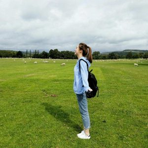 student standing in green field with sheep