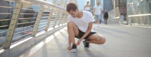 young-man-lacing-shoes-before-running-on-street-in-city