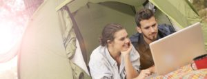 Happy-couple-using-laptop-in-tent