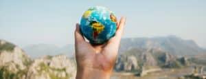 Person-Holding-World-Globe-Facing-Mountain