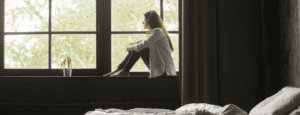 lonely looking student staring out of bedroom window