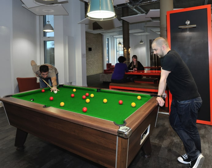 student-playing-pool-in-common-room-692x550
