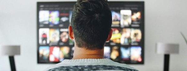 man-choosing-movies-on-screen
