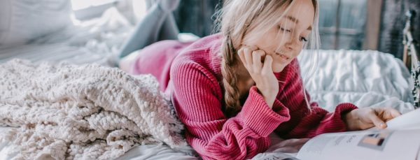 woman-looking-after-wellbeing-reading-on-bed