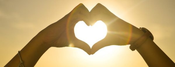 Two-People-Forming-Heart-Sign-to-Sun