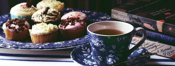 cup of tea cupcakes and books to look after mental health and wellbeing