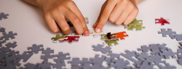 person-trying-to-solve-jigsaw-puzzle