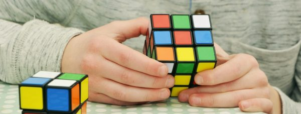 person trying to solve rubiks cub puzzle
