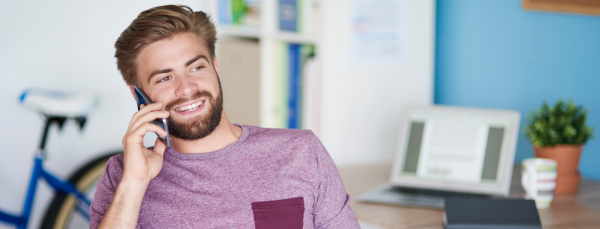 smiling-male-student-on-phone-talking-to-a-mate